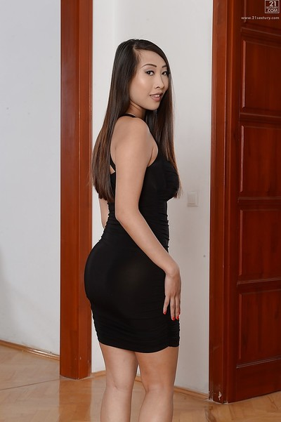 Small Oriental gal Sharon Lee posing wholly covered in fixed ebony clothing