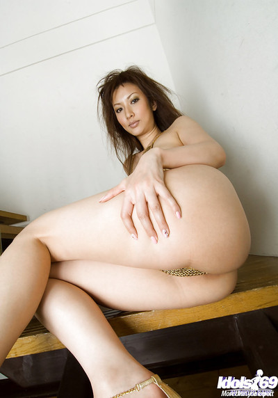 Seductive oriental doll on high heels slipping off her bikini