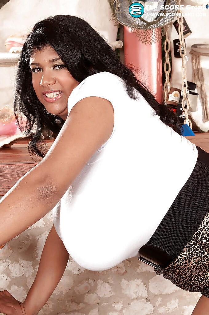 Ebony fatty with big tits Kristina Milan posing in black high heels.