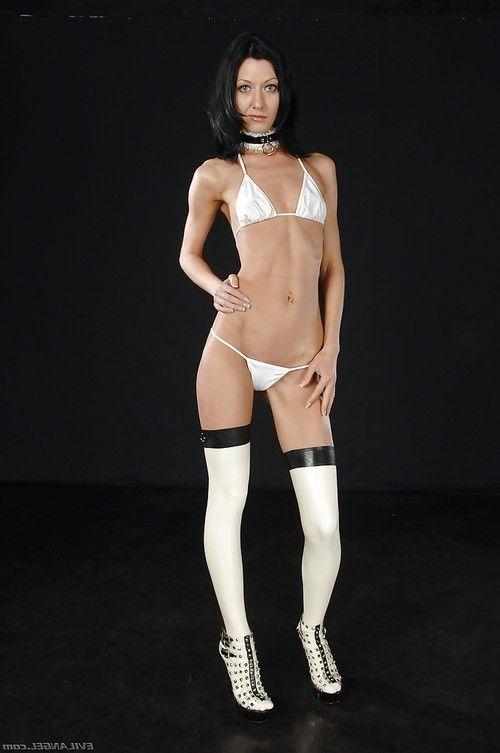 Skinny babe in high heeled latex boots slipping off her bikini