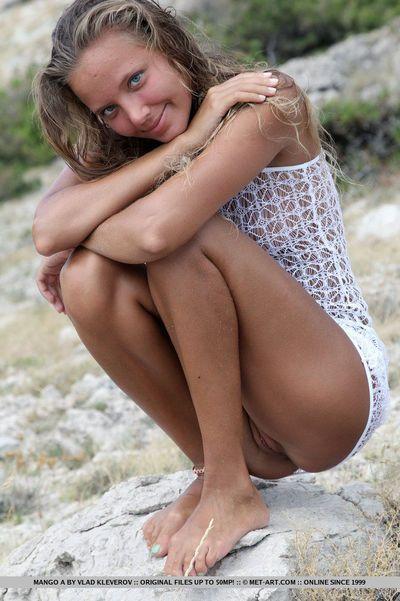Solo girl Mango A modeling naked on rocky beach after disrobing