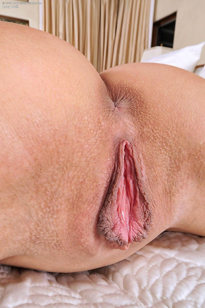 Flexible Latina Lucy Doll posing with a glass dildo in her bald vagina