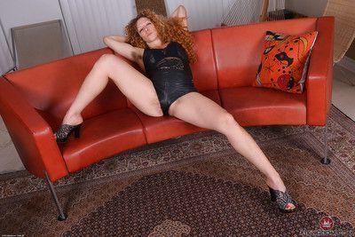 Older hirsute redhead Leona baring big boobs in leather shorts and heels