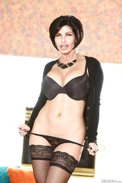 Busty mature woman Shay Fox stripping down to pantyhose and high heels