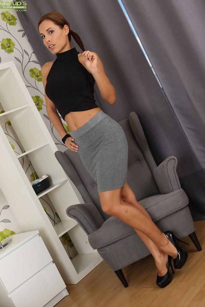 Sexy MILF slides her miniskirt over her bare legs as she gets naked