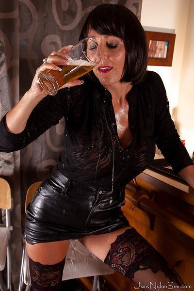 Mature British woman Jan Burton pours a pint of beer over big breasts