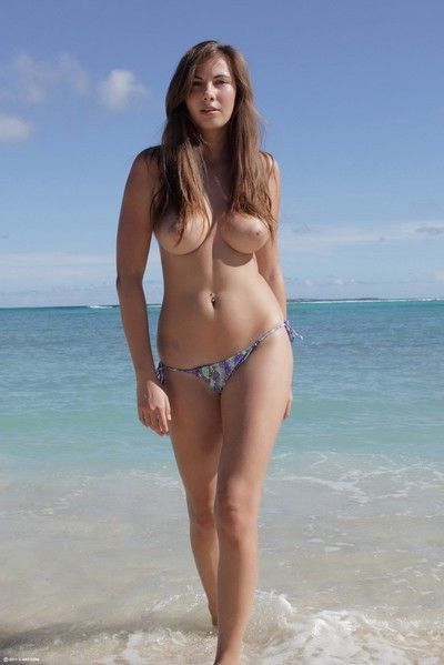 Busty young brunette masturbating in the beach