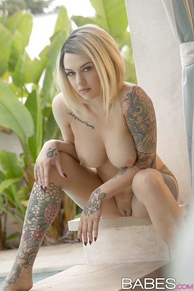 Tattooed blonde girl Emma Mae exposing big tits and thong clad ass outdoors